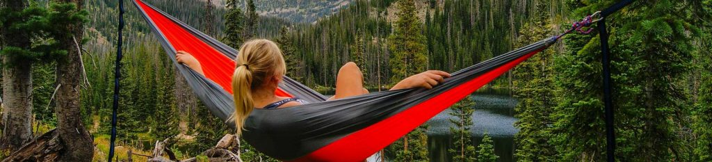Woman relaxing in a camping hammock
