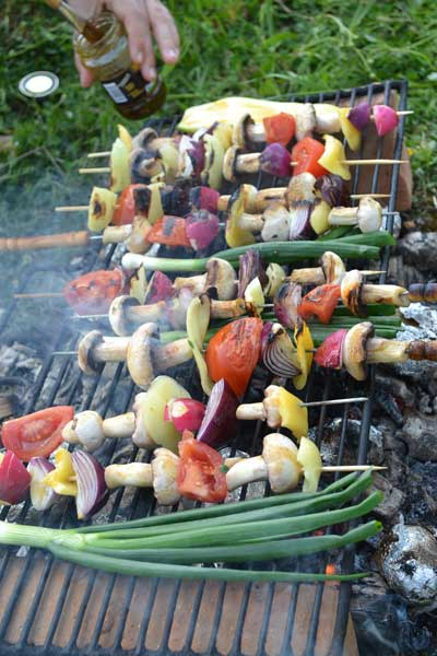 Cooking kabobs over an open fire is one of many easy camping meals for familys