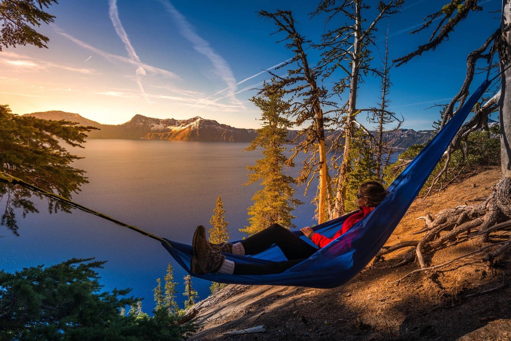 woman in hammock watching sunset over water